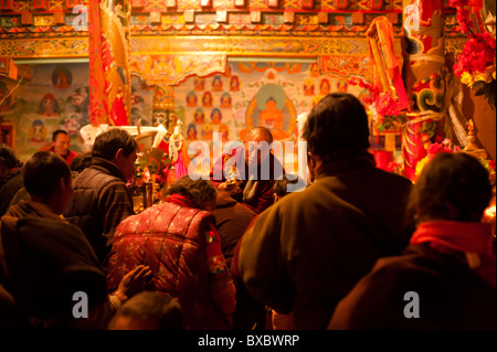 A Tibetan monk blesses lamaist adherents during a ceremony in Tagong Temple, Sichuan province, China. - Stock Photo