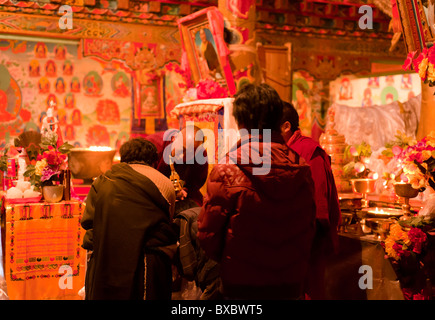 A Tibetan monk blesses lamaist adherents during a ceremony in Tagong Temple, Sichuan province, China - Stock Photo