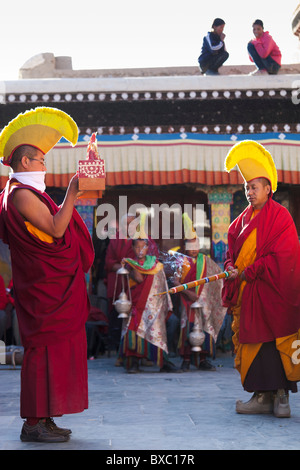 Ladakhi buddhist monks in bright red costumes offering prayers with butter sculpture - Stock Photo