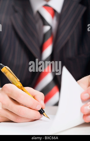 Close up of man's hand signing a document - Stock Photo