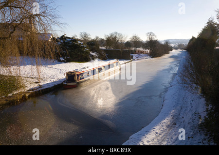 Cheshire England UK December Narrowboat stuck in the ice of a frozen Maccesfield Canal - Stock Photo
