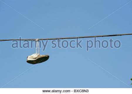 Trainers hanging on a wire above the streets of Madrid in Spain - Stock Photo