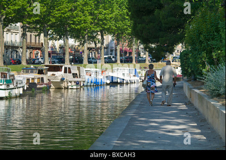 Older Couple Walking on Footpath along the Canal de la Robine Passing Through Narbonne France - Stock Photo