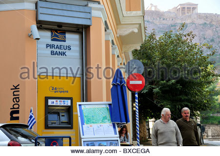 A branch of Piraeus bank in Athens, with the Acropolis in the background - Stock Photo