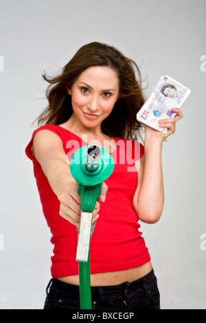 Pretty young female motorist holding a petrol and fuel garage pump and nozzle - Stock Photo