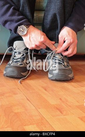 Caucasian Man Tying His Shoelaces on a Pair of Trainers ( Sneakers ), UK MODEL RELEASED - Stock Photo