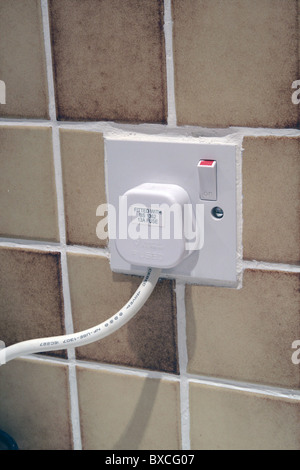 A Three Pin UK Electrical Plug Plugged into a Wall Socket with the power supply switched on - Stock Photo