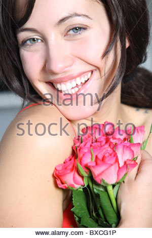portrait of brunette woman holding red roses in hands - Stock Photo