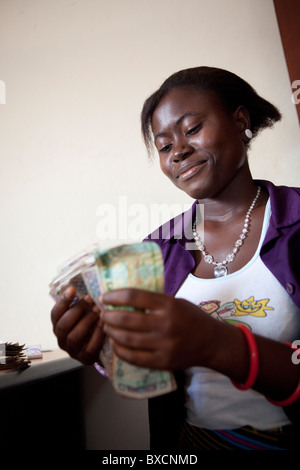 A woman counts cash after receiving a microfinance loan in Freetown, Sierra Leone, West Africa. - Stock Photo