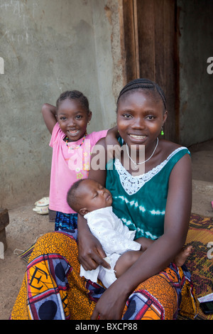 A young mother and her two children sit together on their porch in Port Loko, Sierra Leone, West Africa. - Stock Photo