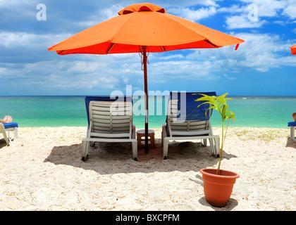 Beach chairs under an umbrella at the long white sand beach in Flic en Flac, Black River, Mauritius - Stock Photo