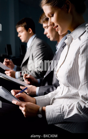 Portrait of business people writing a text at seminar in the evening - Stock Photo