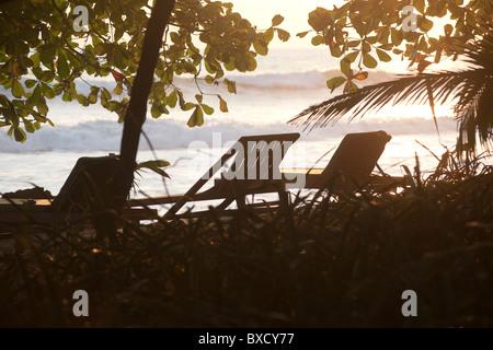 Lounge chairs along Mal Pais coastline in San Jose Costa Rica - Stock Photo