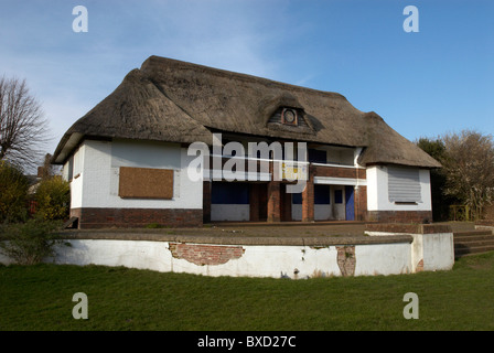 Abandoned thatched roof sports pavillion building Norwich United Kingdom - Stock Photo