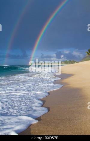 An amazing double rainbow over Rocky Point, on the north shore of Oahu, Hawaii. - Stock Photo