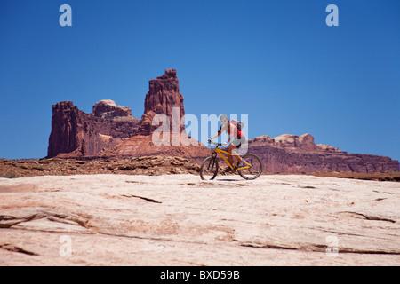 A woman bikes the White Rim trail in Utah. - Stock Photo