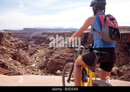 A woman bikes the White Rim trail in Utah. - Stock Photo