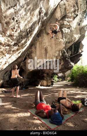 A caucasian male climber falls on lead while belayer catches and two women watch. - Stock Photo