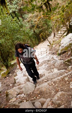 A male trekker ascends stone steps in Nepal. - Stock Photo