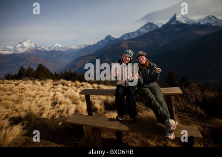 A trekking couple adjust their hats infront of the Annapurna mountain range in Nepal. - Stock Photo