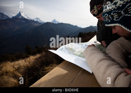 A trekking couple study a map from a viewpoint of Annapurna South in Nepal. - Stock Photo