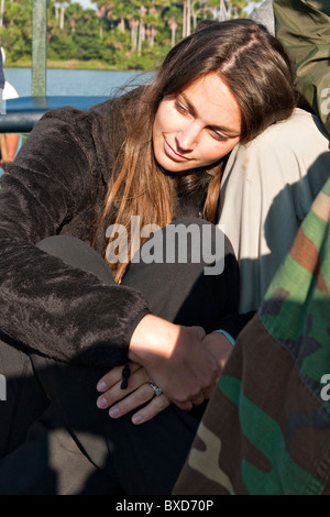 A young woman smiles as she rests and reflects on the day during sunset in the amazon. - Stock Photo