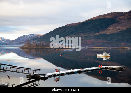 Small Boat On Loch Lomond Scotland With Reflections and smoke - Stock Photo