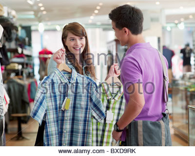 Couple shopping for shirts in store - Stock Photo