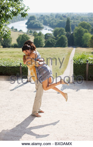 Playful, happy couple hugging outdoors - Stock Photo