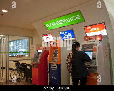 Women using an ATM machine at the ATM Service center area in MBK Shopping mall. - Stock Photo