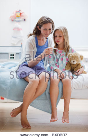 Mother checking daughter's temperature with digital thermometer - Stock Photo