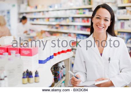 Pharmacist standing in drug store - Stock Photo