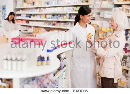 Pharmacist talking to customer in drug store - Stock Photo