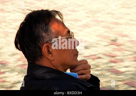 Asian man sitting on park bench in Hong Kong China - Stock Photo