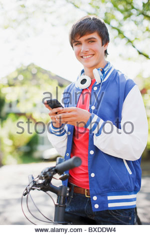 Smiling teenage boy with bicycle text messaging on cell phone - Stock Photo