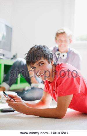 Smiling teenage boy laying on floor text messaging on cell phone - Stock Photo