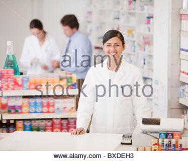 Pharmacist standing at cash register in drug store - Stock Photo