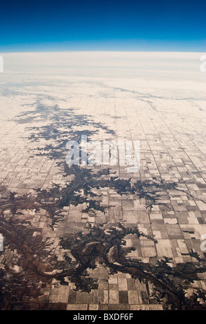 Aerial photo somewhere over the Midwestern USA after a winter snowfall, clearly showing grid layout of farmland. - Stock Photo