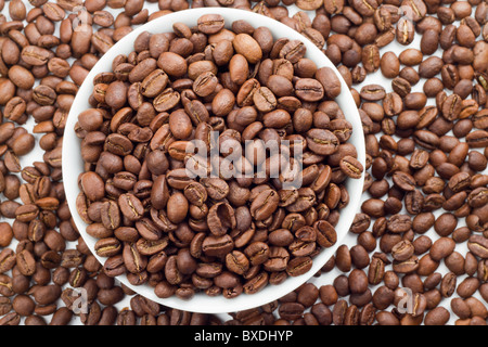 Close up of Coffee beans in bowl and around a white bowl - Stock Photo