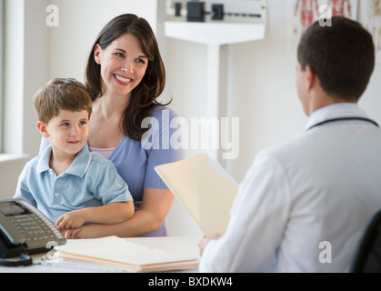 Doctor talking to woman and her son - Stock Photo