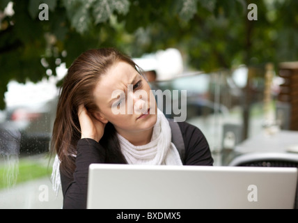Stressed young woman with a laptop outdoor - Stock Photo