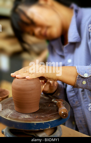 Asian woman moulding clay on a pottery wheel - Stock Photo