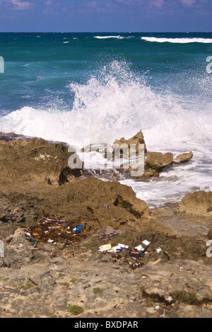 Trash scattered on a beautiful rocky beach in Jamaica - Stock Photo