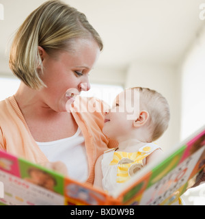 Mother reading book to her baby daughter - Stock Photo