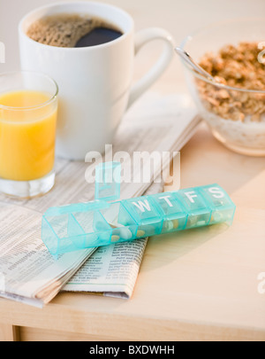 Prescription pills on breakfast table - Stock Photo