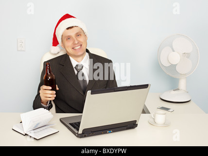 A young businessman gets drunk at the office before the new year - Stock Photo