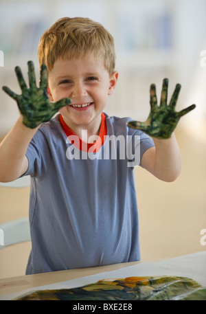 Young boy finger painting - Stock Photo