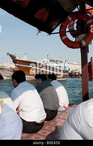 People on an Abra traditional boat on the Creek in Dubai - Stock Photo