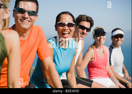 Runners resting on the side of the road - Stock Photo
