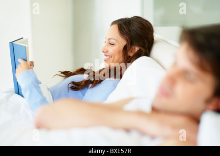 Woman reading book in bed beside sleeping husband - Stock Photo